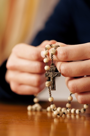 rosary beads: Woman (only close-up of hands to be seen) with rosary sending a prayer to God, the dark setting suggests she is sad or lonely  Stock Photo