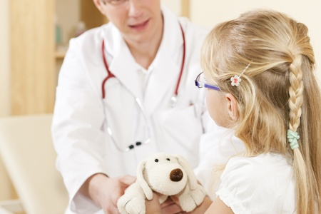 paediatrician: Doctor - Pediatrician - with a child patient in his practice, she is giving him her soft toy as to thank him