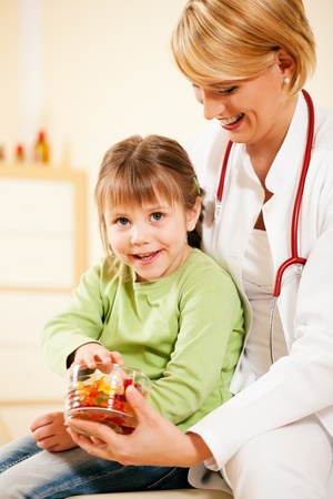 Female pediatrician doctor giving candy (gummy bears) to little patient after the treatment  photo