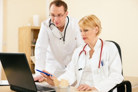 health management: Two doctors - male and female - discussing documents in their practice, test reports or maybe administrative or financial stuff