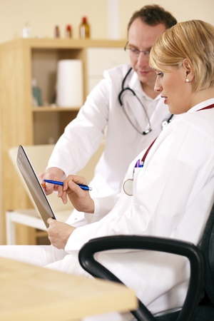 Two doctors - male and female - discussing documents in their practice, test reports or maybe administrative or financial stuff  photo