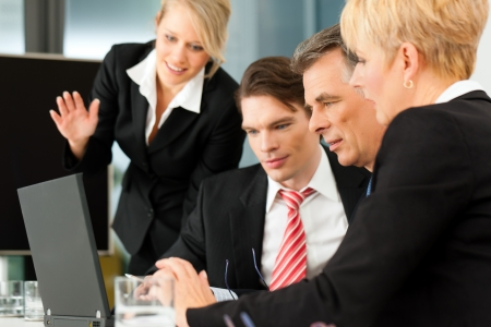 Business - team meeting in an office with laptop, the boss with his employees Stock Photo - 10965383