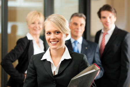 expert: Business - team in an office; the junior manager is standing in front