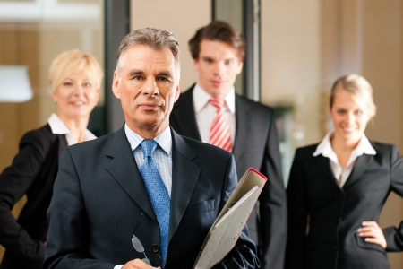 confident consultant: Business - team in an office; the senior executive is standing in front