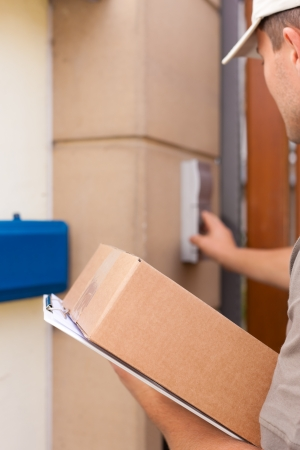 Postal service - delivery of a package; the postman is standing in front of the door and rings the bell Stock Photo - 10965257