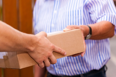 delivery package: Postal service - delivery of a package; the postman is giving the package to the customer in front of his house  Stock Photo