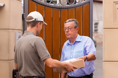 mail man: Postal service - delivery of a package; the postman is giving the package to the customer in front of his house  Stock Photo