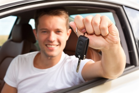 new automobiles: Man is holding his car key sitting himself in the automobile and obviously has fun