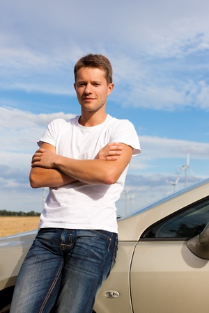 Man leaning on his car; presumably he has a break from driving photo