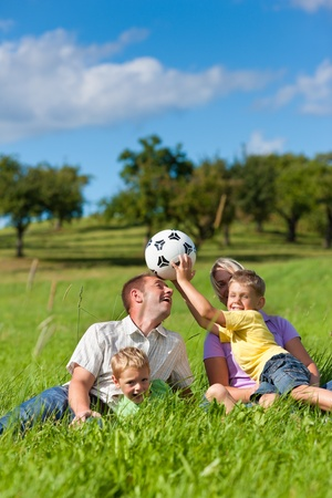 Family with two little boys playing in the grass on a summer meadow - they have a football