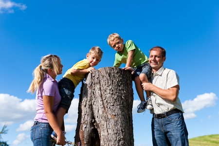 playing field: Happy family on excursion in summer - they discovered a trunk Stock Photo