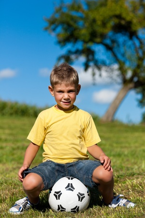 child ball: happy little boy with football sitting on a meadow and is playing with it