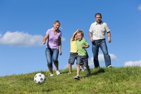 hermanos jugando: Familia feliz con dos niños jugando fútbol en la hierba en un prado de verano