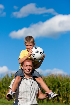 father and son: Father and son with football; he is carrying the son on the shoulders