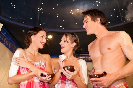 two women and one man: Three friends - two women, one man - doing wellness in the sauna of a thermal bath Stock Photo