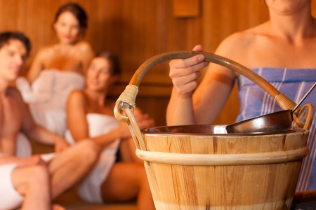 Four friends - three women, one man - doing wellness in the sauna of a thermal bath photo