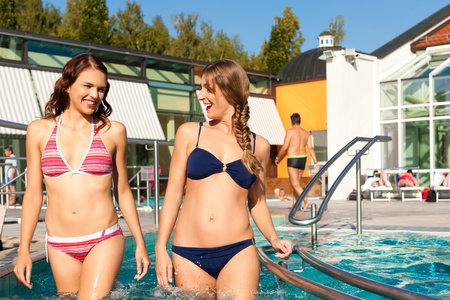 sun bathing: Two happy young women wading water in hydrotherapy in a health spa Stock Photo