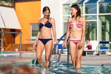 bikini pool: Two happy young women wading water in hydrotherapy in a health spa Stock Photo