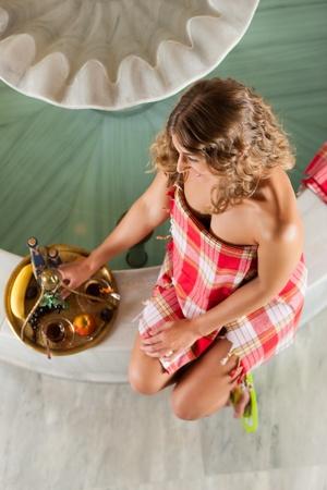 fruitmand: Wellness - een vrouw is ontspannen in ontspanningsruimte met thee en fruitmand