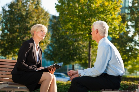 Coaching outdoors - a man and a woman have a coaching discussion Stock Photo
