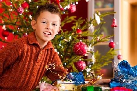 Christmas - happy little boy with Xmas present on Christmas Eve photo