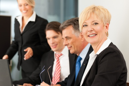 expertise: Business - team meeting in an office with laptop, the boss with his employees, one woman is looking into the camera Stock Photo