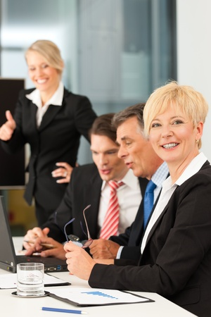 four person: Business - team meeting in an office with laptop, the boss with his employees, one woman is looking into the camera Stock Photo