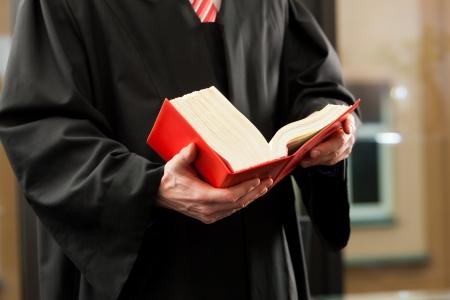 ley: Abogado con el c�digo de derecho civil en una sala del tribunal, primer plano, s�lo el torso para ser visto