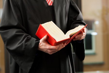 Lawyer with civil law code in a court room, close-up, only torso to be seen Stock Photo