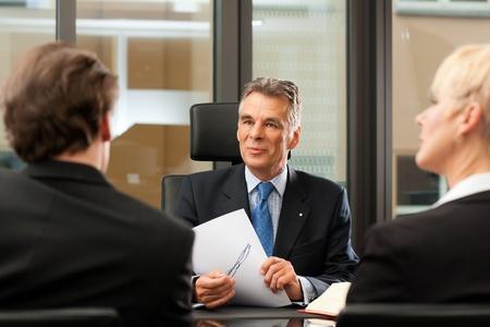 n�gociation: Mature avocat ou un notaire avec les clients dans son bureau � une r�union Banque d'images