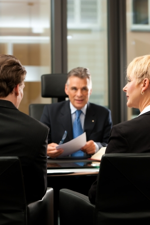 Mature lawyer or notary with clients in his office in a meeting photo