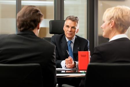 Abogado o notario mayor con los clientes en su oficina en una reunión