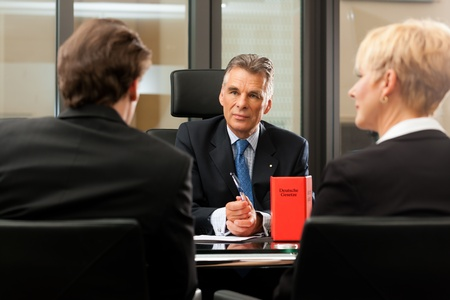 law: Mature lawyer or notary with clients in his office in a meeting