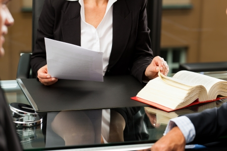 law: Mature female lawyer or notary with client in her office for counseling