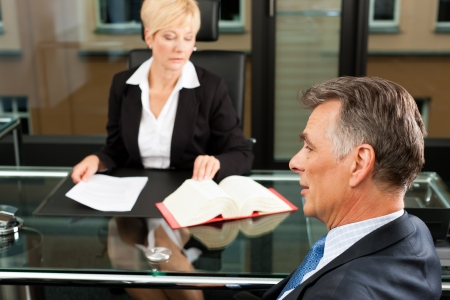 arbitrate: Mature female lawyer or notary with client in her office for counseling