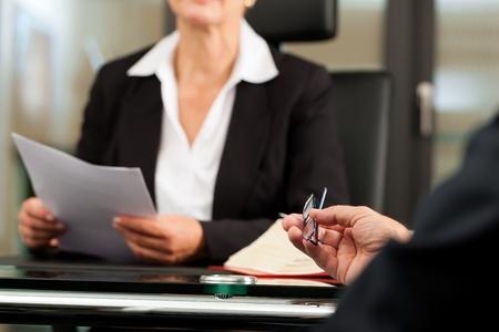 ley: Abogado o notario de hembras maduras con el cliente en su oficina para recibir asesoramiento Foto de archivo