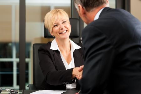 Abogado o notario de hembras maduras con el cliente en su oficina - apretón de manos
