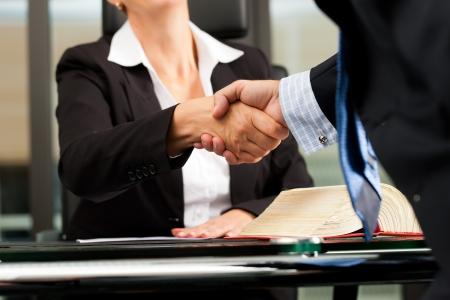 Rijpe vrouwelijke advocaat of notaris met de cliënt in haar kantoor - handdruk