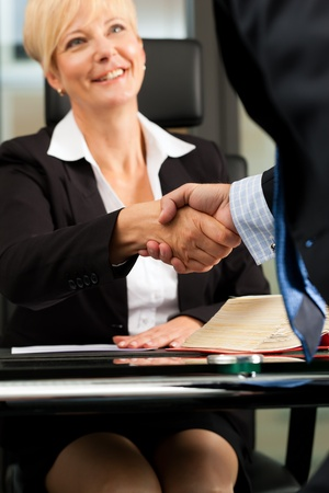 lawyer: Mature female lawyer or notary with client in her office - handshake