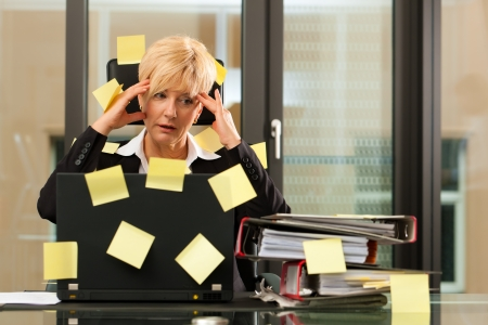 timemanagement: Een vrouw heeft stress in het kantoor - multitasking en time management Stockfoto