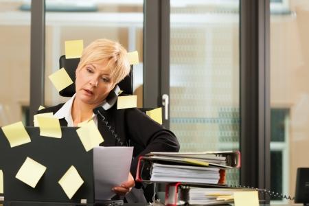 gestion del tiempo: Una mujer tiene el estrés en la oficina - la multitarea y la gestión del tiempo