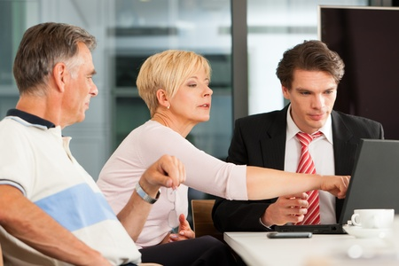 financial adviser: Mature couple with young financial consultant - they are planning their retirement Stock Photo