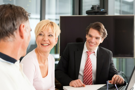 Mature couple with young financial consultant - they are planning their retirement photo