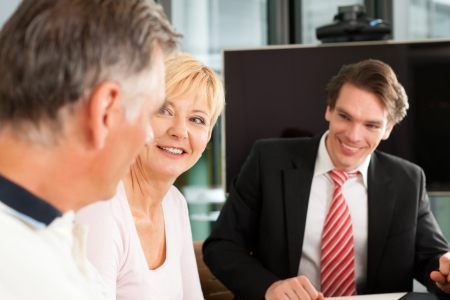 financial assets: Mature couple with young financial consultant - they are planning their retirement Stock Photo
