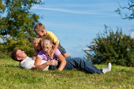 Happy family with two little boys playing in the grass on a summer meadow  photo