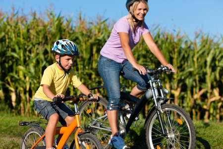 Family is cycling in summer - here mother with son photo