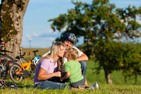 Happy family (father, mother and son) on getaway with bikes - they have a break photo