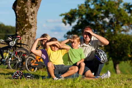 dazzled: Happy family (father, mother and two sons) on getaway with bikes - they have a break