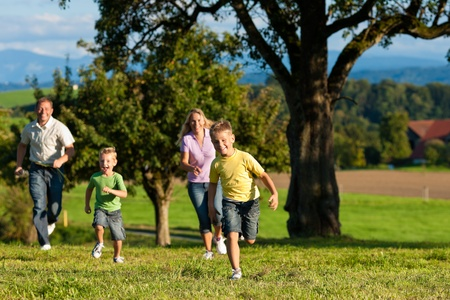 family health: Happy family outdoors is running on a meadow on a beautiful summer day - they try to catch each other