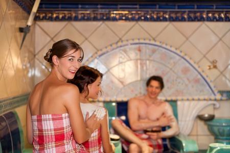 Three friends - two women, one man - doing wellness in the sauna of a thermal bath photo
